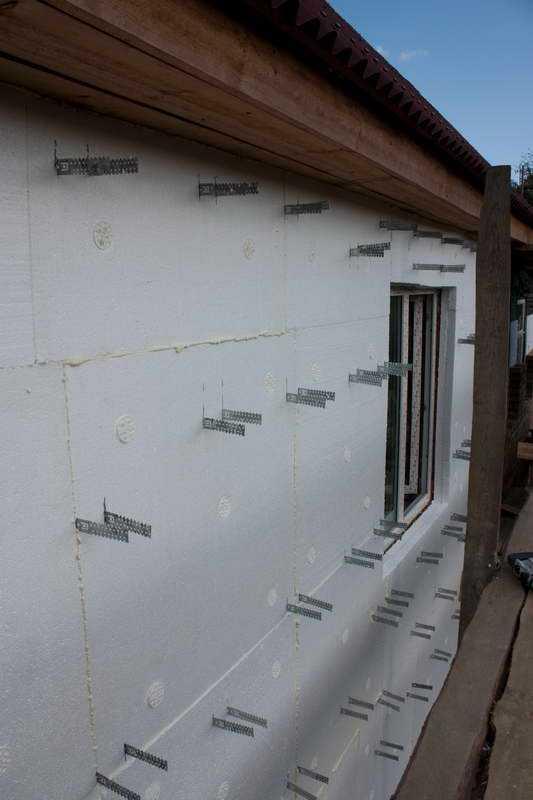 Процесс крепления пенополистирола к стене с подготовительного этапа